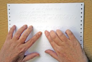 two hands reading braille on wooden desk