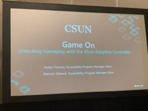 "Large screen with slide saying ""Game On:  Unlocking Gameplay with the XBox adaptive Controller"""