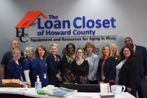 Group of 12 people gathered in front of Loan Closet Logo on wall.