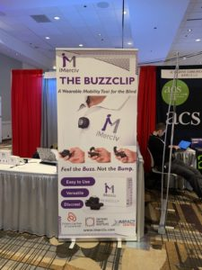 Large product sign for BuzzClip device in front of conference table.