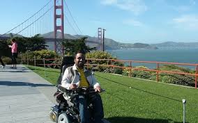 Man using wheelchair outside on path with Golden Gate Bridge in background.