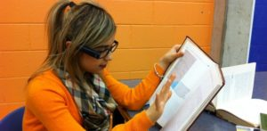 Girl reads book using OrCam wearing glasses.