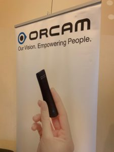 """Close up of OrCam poster.  Says """"ORCAM, Our Vision.  Empowering people.  Shows a hand holding device."""