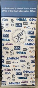 Large sign with Dept of Human Services logo in center surrounded by logos of all agencies in department