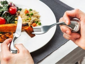 Close up of two hands holding fat handled silver fork and knife. Fork has piece of potato on it.