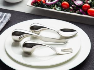 Close up of white plate with fork, spoon and knife in silver with fatter handles on plate.