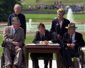 President Bush signing ADA law with four onlookers.