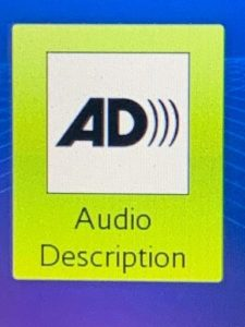 close up of blue and green logo of audio description