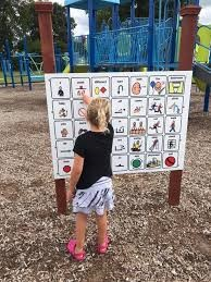 Small girl points at picture on white board in playground