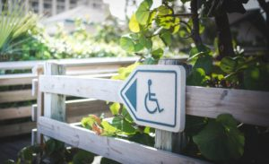 White and blue directional sign with wheelchair ADA logo
