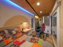 This is a photograph of a wheelpad bedroom. This photograph exhibits a room with a bed, a nightstand, and a wheelchair positioned by the bed and nightstand. The bed has a colorful quilt on it with squares of purple, green, blue, and orange. The ceiling has circular lights that go down length of the room.
