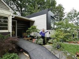 This photograph portrays a woman in a blue/purple sweater standing outside of the wheelpad. This wheelpad is attached to a host house with a connecting walkway built into the side of the wheelpad. This shows a black ramp that is built up to enter the connecting strcuture. There are trees and plants all outside of the wheelpad and the host house.